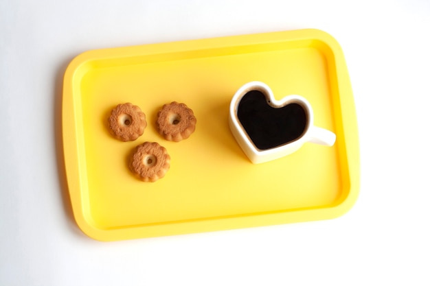 Biały kubek w kształcie serca z kawą i ciasteczkami na żółtej tacy, widok z góry