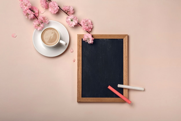 Biały kubek z cappuccino, kwiatami sakury, tablica kredowa na pastelowym różowym tle.
