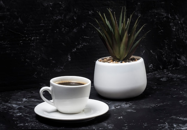 Biały kubek z czarną aromatyczną kawą na czarnym tle streszczenie z kwiatem doniczkowym w tle.