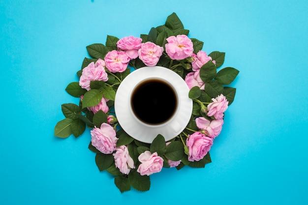 Biały kubek z czarną kawą i różowymi różami wyłożonymi wokół na niebieskim tle.