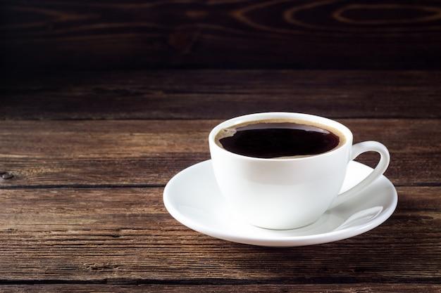 Biały kubek z czarną kawą na drewnianym stole