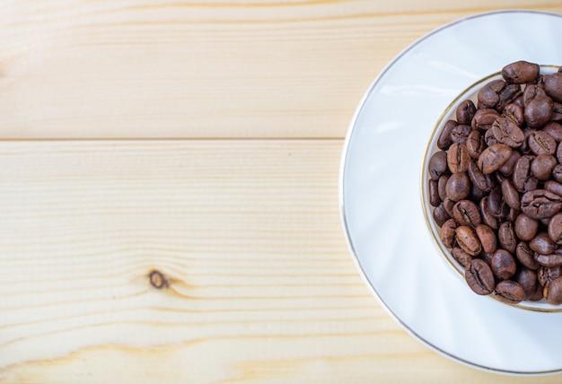 Biały kubek z filiżanką ziaren kawy na drewnianym tle z selektywnym focusem i fragmentem upraw.