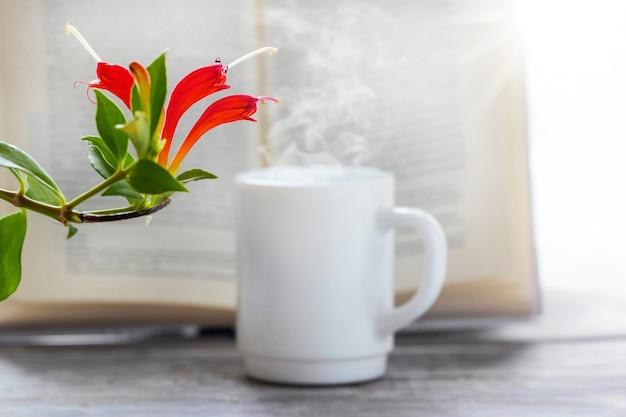 Biały kubek z gorącą kawą w pobliżu otwartej książki i rośliny doniczkowej z kwiatami