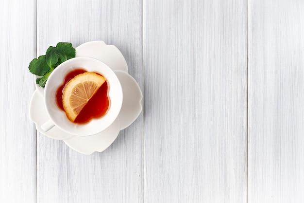 Biały kubek z herbatą miętową i cytrynowym widokiem z góry na białym drewnianym stole poziomym bez ludzi