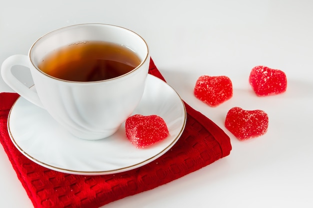 Biały kubek z herbatą na czerwonej serwetce i marmoladzie w kształcie serca na białym tle. symbol miłości, walentynki, karta podarunkowa