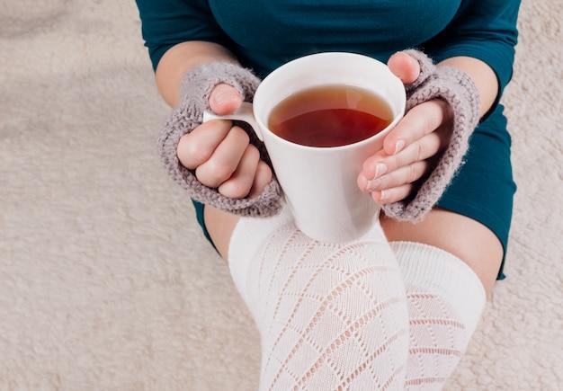 Biały kubek z herbatą w rękach dziewczynki