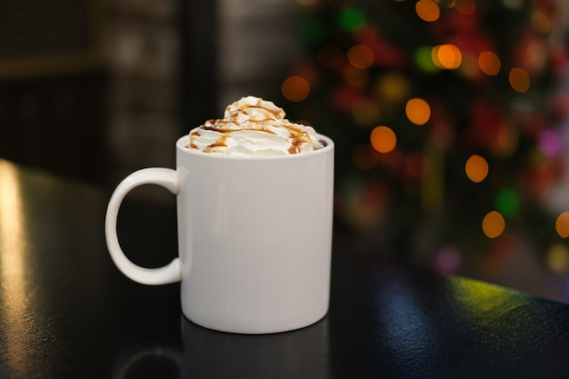 Biały kubek z kakao lub kawą ze śmietaną z syropem karmelowym w kawiarni na tle girland bokeh z choinki. cappuccino lub lat z polewą w filiżance.