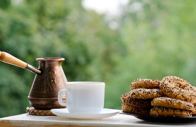 Biały kubek z kawą, cezve i talerz ciasteczek na stole