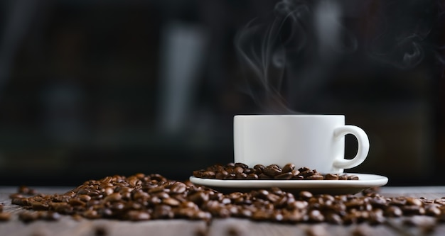Biały kubek z kawą espresso i ziarnami na drewnianym stole ciemny