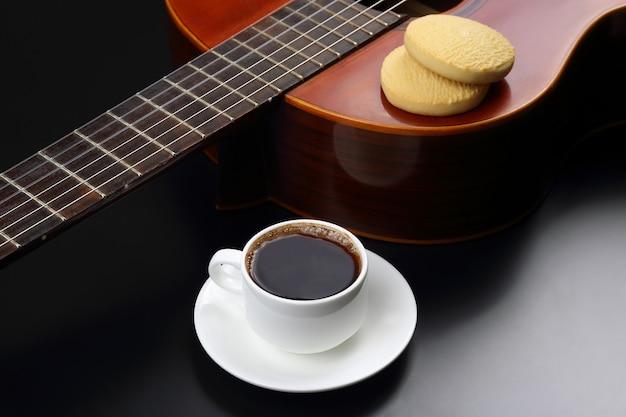 Biały kubek z kawą i ciastkami na gitarze akustycznej