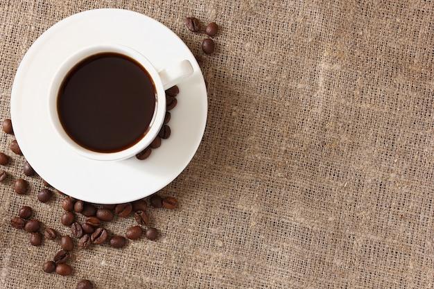 Biały kubek z kawą, spodkiem i porozrzucanymi ziarnami kawy na szorstkim płótnie obrus, widok z góry.