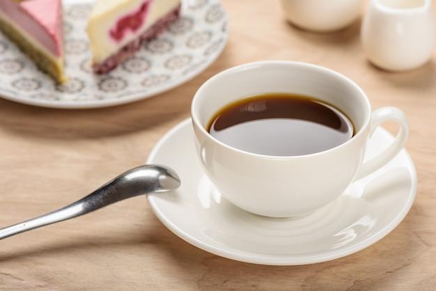 Biały kubek z napojem na spodeczku na drewnianym stole na tle kawałków ciasta.
