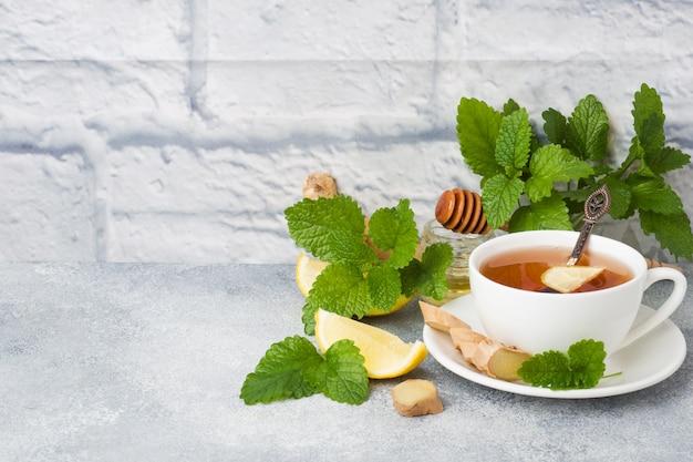 Biały kubek z naturalną herbatą ziołową imbirowo-cytrynową miętą i miodem.