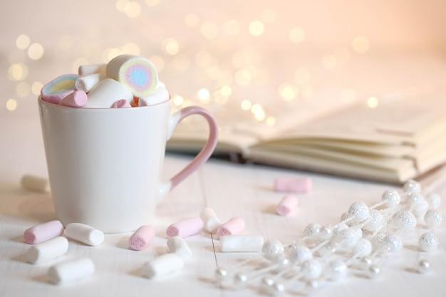 Biały kubek z piankami i książką na stole