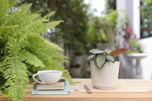 Biały kubek z zeszytami i ołówkiem z doniczką na drewnianym stole na zewnątrz zielonego zewnętrznego domu