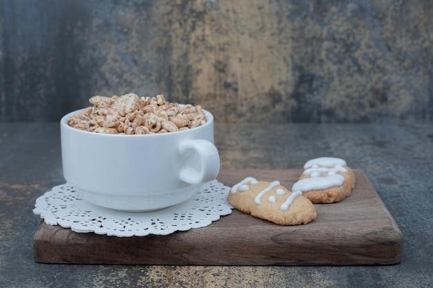 Biały kubek ze świątecznymi ciasteczkami na drewnianej desce