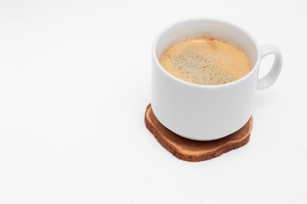 Biały kubek ze świeżą czarną kawą americano na drewnianym szlifie w kształcie koła.