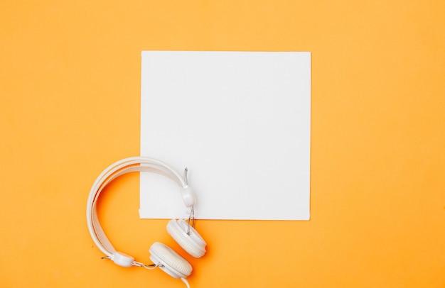 Biały kwadratowy karton i słuchawki na żółto