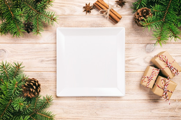 Biały kwadratowy talerz na drewnianym stole z boże narodzenie dekoracją