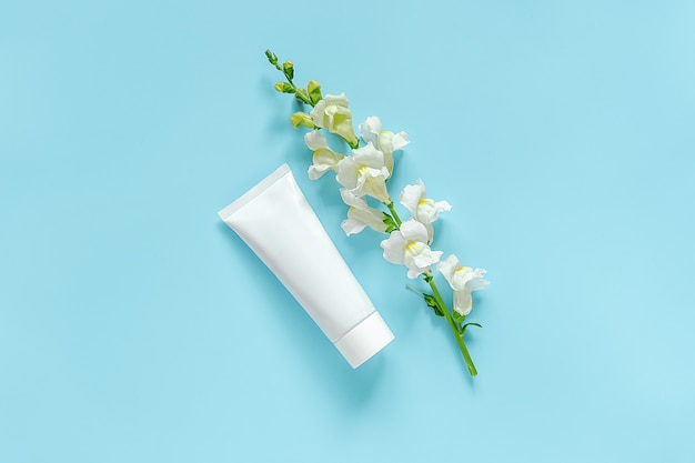 Biały kwiat i kosmetyk, biała tubka medyczna do kremu, maści, pasty do zębów. naturalne kosmetyki organiczne