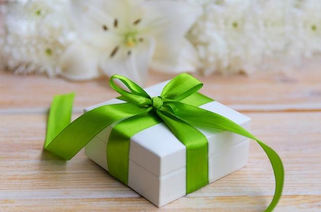 Biały kwiat lilii i białe pudełko z zieloną wstążką i łuk na jasnym tle drewnianych. piękna kartka z pozdrowieniami. szczęśliwy dzień matki lub koncepcja happy birthday.
