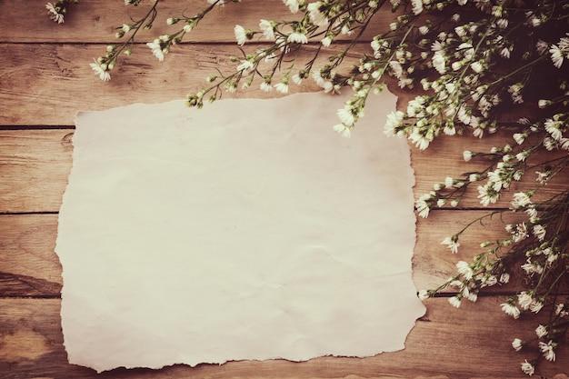 Biały kwiat na pokładzie drewna grunge i papieru tła z miejsca.