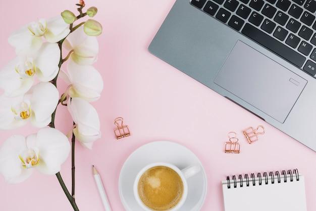 Biały kwiat orchidei; notes spiralny; ołówek; filiżanka kawy; laptop i spinacz do papieru na różowym tle