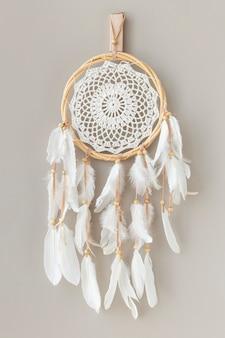 Biały łapacz snów wiszący na białej ścianie