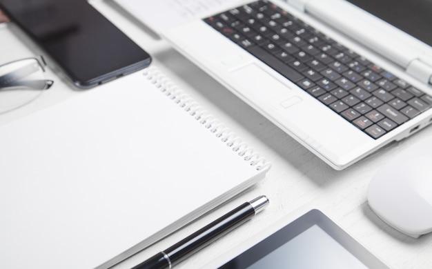 Biały laptop i obiekty biznesowe na białym biurku.