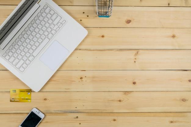 Biały laptop z inteligentnego telefonu, karty kredytowej i modelu wózek na zakupy na tle drewniany stół. zakupy w e-commerce.