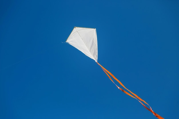 Biały latawiec czerwony tailed lecący na tle błękitnego jasnego nieba.