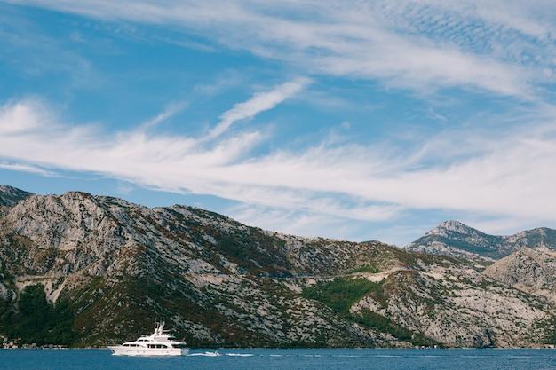Biały luksusowy jacht pływa po zatoce kotorskiej w czarnogórze na tle gór