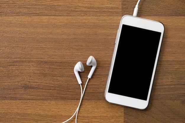 Biały mądrze i słuchawki na drewnianym tle