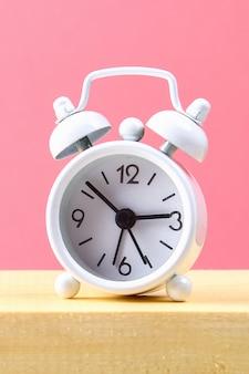 Biały mały budzik na drewnianej półce w różowym pastelowym kolorze. minimalizm.