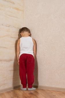 Biały mały chłopiec stoi drewniane ściany. bardzo nieśmiały patrząc na kamerę