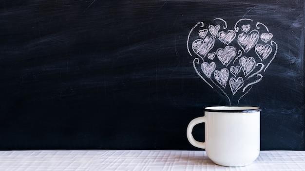 Biały metalowy kubek i rysowane kredą małe serca w formie serca