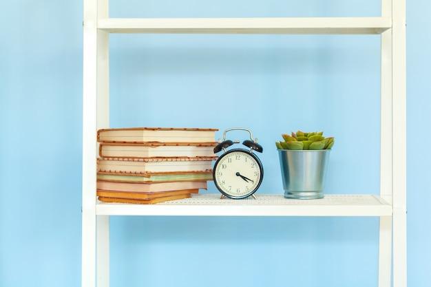 Biały metalowy stojak z książkami na niebieskim tle