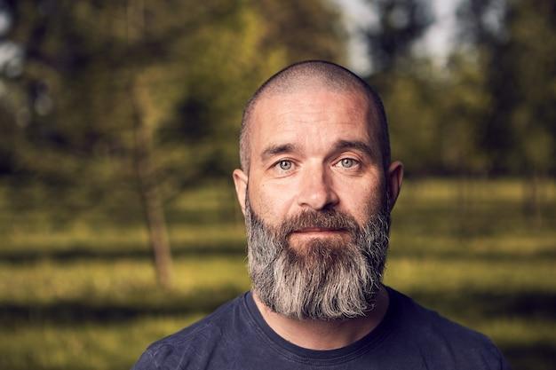 Biały mężczyzna około 43 lat z krótkimi włosami i brodą odpoczywa w parku z bliska.