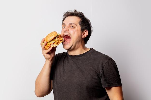 Biały mężczyzna w czarnej koszulce z burgerem na białej ścianie
