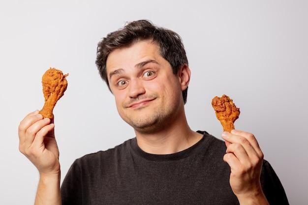 Biały mężczyzna w czarnej koszulce z podudziami kurczaka na białej ścianie