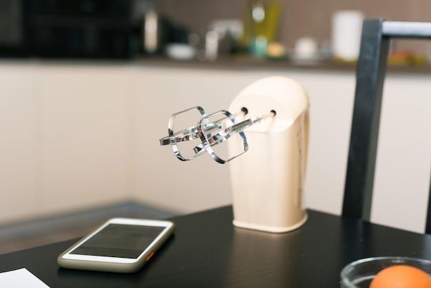 Biały mikser i smartfon na czarnym stole w kuchni