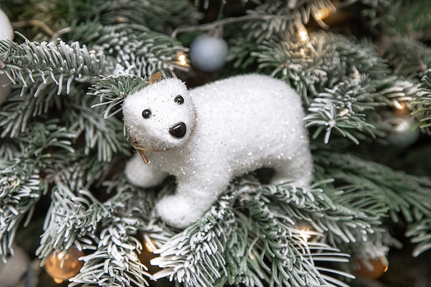 Biały miś siedzący na choince w śniegu, wystrój choinki, świąteczna koncepcja, światła