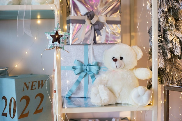 Biały miś siedzi na półce obok pudełek napis nowość 2022