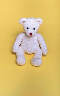 Biały miś siedzi na żółtym tle. z miejscem na kopię. najlepszy przyjaciel dzieci. pierwszoplanowy. ścieśniać.