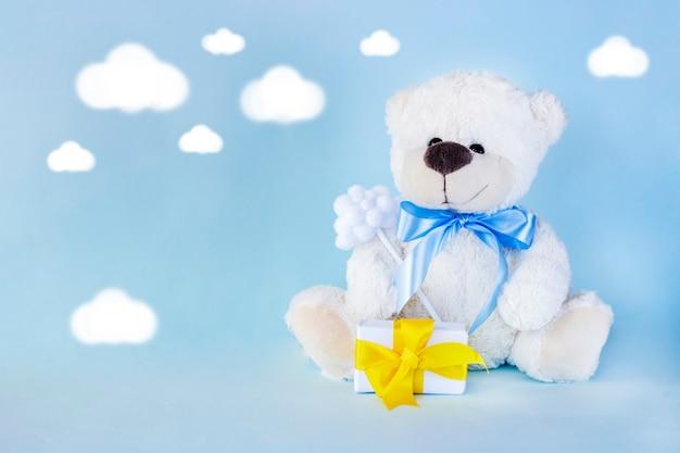 Biały miś trzymający mały prezent w postaci chmurki z żółtą wstążką na jasnoniebieskim tle