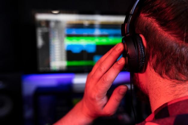 Biały młody dj miksuje w programie dźwiękowym nowy utwór w studiu stereo za pomocą miksera i mikrofonu.