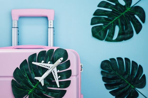 Biały model samolotu na różowym bagażu z liśćmi palmowymi na niebiesko pastelowych kolorach podróży i letniej plaży