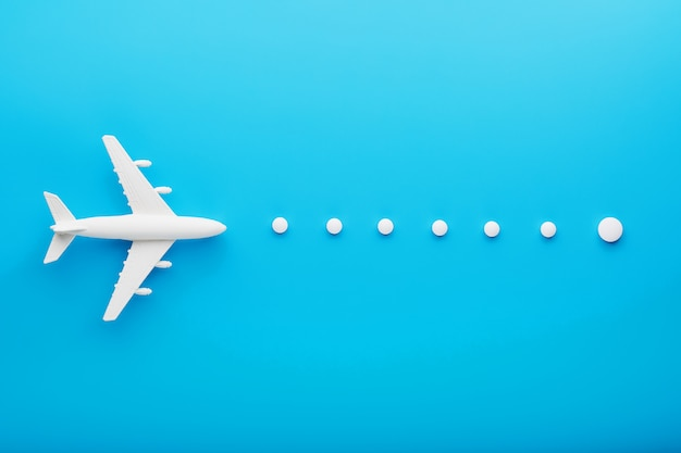 Biały model samolotu pasażerskiego z kropkowanymi punktami trajektorii na białym tle