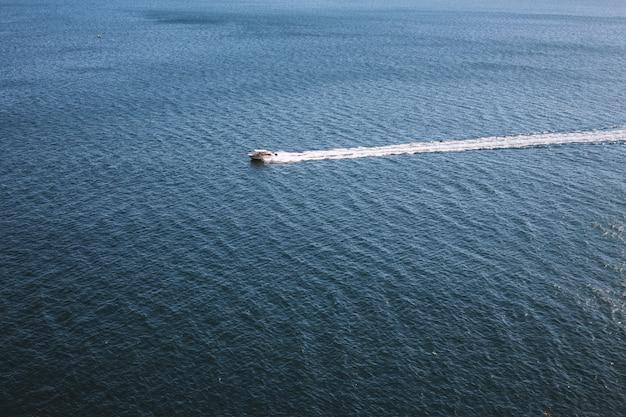 Biały motorowy łódkowaty statek na wody morskiej powierzchni