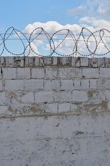Biały mur z drutu kolczastego brzytwa z błękitne niebo i chmury za ścianą na tle. koncepcja wolności